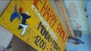 Ein Schild muss her! Damit auch alle finden wonach sie suchen, werden Schilder gemalt, die zu One Happy Family führen.